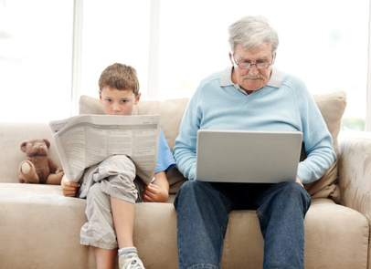 Old man using a laptop with his grand son reading a newspaper - Indoor